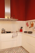 Modern white kitchen with red walls and patterned floor