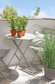 Grey folding table and chairs on balcony with patterned floor tiles and plants