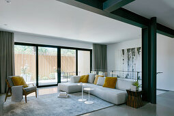 White sofa with yellow scatter cushions in living room with black beams