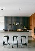Three black barstools at rectilinear kitchen island