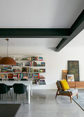 Dining table in front of bookshelves in modern interior