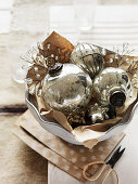Vintage silver Christmas-tree baubles in ceramic bowl