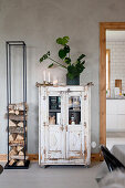 Old glass-fronted cabinet next to modern firewood rack
