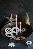 Zwei brennende Kerzen in einer Schale mit Anhängern aus Modelliermasse