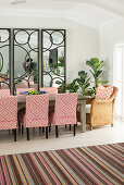 Upholstered chairs around dining table in front of three large mirrors with pattern of circles