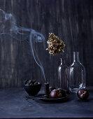 Stillleben mit dunklem Obst, Glasflaschen und Kerzenrauch
