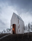 Modernes Haus mit Holzfassade und vertikalen Fenstern auf einem Hügel