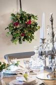 Handmade Christmas wreath with roses on wall behind festively set table