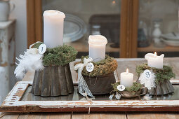 Adventskranz aus vier Kerzen auf alten Backformen mit Moos