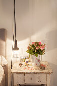 Bouquet of roses in coffee jug on old bedside table