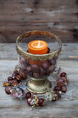 Candle and horse chestnuts in glass goblet and wreath handmade from horse chestnuts