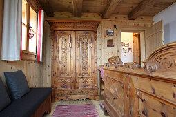 Kleiderschrank und Doppelbett mit Holz-Fußteil im Hütten-Schlafzimmer
