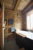 Bathtub and towel rail in rustic, wood-clad bathroom