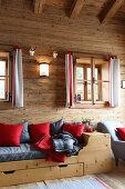 Holzbett mit roten und grauen Kissen in einer Holzhütte