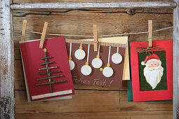 Handcrafted Christmas cards pegged to strings in old window frame