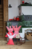 Hand-sewn Christmas angels on sledge in front of tiled stove