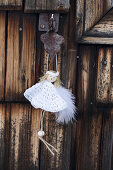 Handmade angel in white dress hung from wooden door