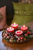 Advent candles, walnuts and conifer sprigs in dish