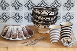 Advocaat cake, bowls and beakers on wooden surface