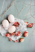 Roses and white eggs on muslin amongst twigs