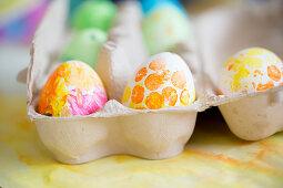 Mit Gouache-Farben bemalte Ostereier im Eierkarton