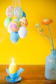 Mit Gouache-Farben bemalte Ostereier, Kerze und Blumenvase