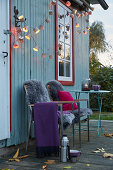 DIY fairy lights made from paper baking cases, a plaid and sheepskins on garden chairs