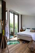 Double bed, wooden floor with glass insert and open balcony doors in bedroom