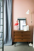 Standard lamp next to vases, mirror and flamingo ornament on top of chest of drawers against pink wall