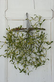 Branch of mistletoe hung from old cupboard door by gingham ribbon
