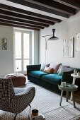 Various upholstered furniture in living room with wood-beamed ceiling