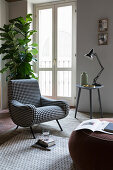 Checked armchair in front of fiddle leaf fig and floor-to-ceiling window