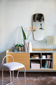 Pink metal chair in front of sideboard with open-fronted compartments
