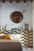 Round mirror above protruding wall section used as bed headboard