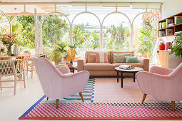 Living room in pastel shades with glass wall leading to Mediterranean garden
