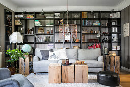 Grey couch, wooden block used as coffee table and floor-to-ceiling bookshelves in living room