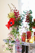 Christmas decoration with anemones, candles and fairy lights on mantelpiece
