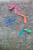 Gebastelte Libellen aus bemalten Ahornsamen auf einem Holz