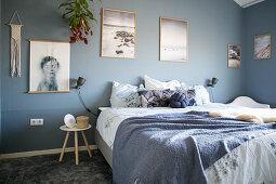 Doppelbett und großformatige Fotos im Schlafzimmer mit grau-blauen Wänden