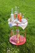 Erfrischungsgetränke in Flaschen und zarte Kirschblüten auf rundem Beistelltisch im Garten