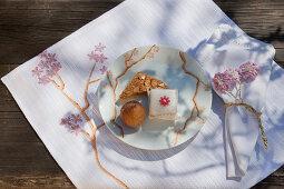DIY-Tischset mit Kirschblütenmotiv, Gebäck und Petit Four auf Kuchenteller