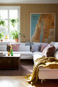Sunlight falling into vintage-style living room with map on wall