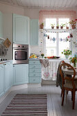 Cosy kitchen-dining room with pale blue country-house-style cabinets