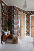 Bright, floral wallpaper and white board floor in hallway