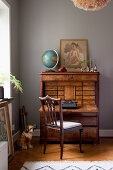 Antique bureau and vintage-style accessories against grey wall