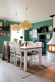 Petrol-blue walls and wood-fired stove in dining room