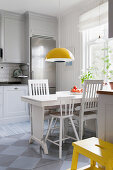 White wooden table and chairs below pendant lamp in kitchen-dining room