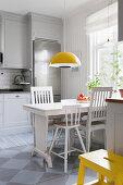 Weißer Holztisch mit Stühlen, darüber Hängelampe in Wohnküche