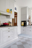 Pale grey fitted kitchen with painted board floor
