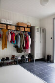 Coat rail, shoe racks and metal locker in cloakroom in hallway